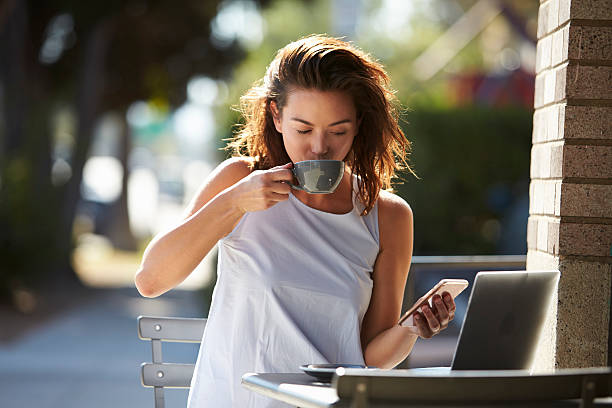 Woman using smartphone and laptop drinking coffee outside stock photo