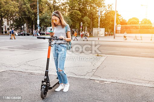 874772840istockphoto Woman using smartphone and renting modern electric scooter with an application. Urban transport concept 1186106495