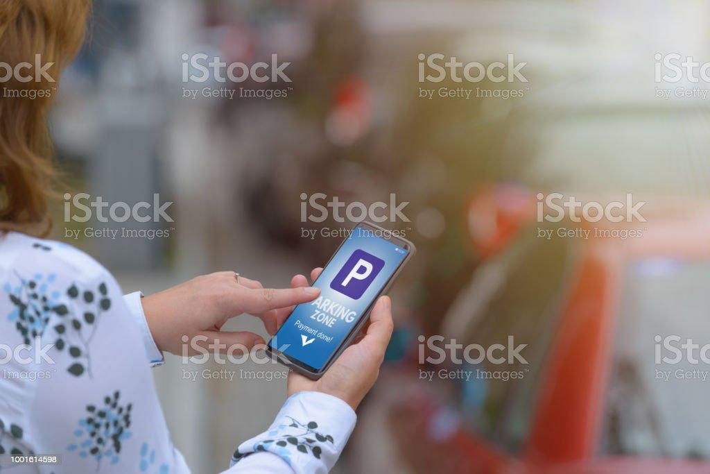 Woman using smartphone app to pay for parking stock photo