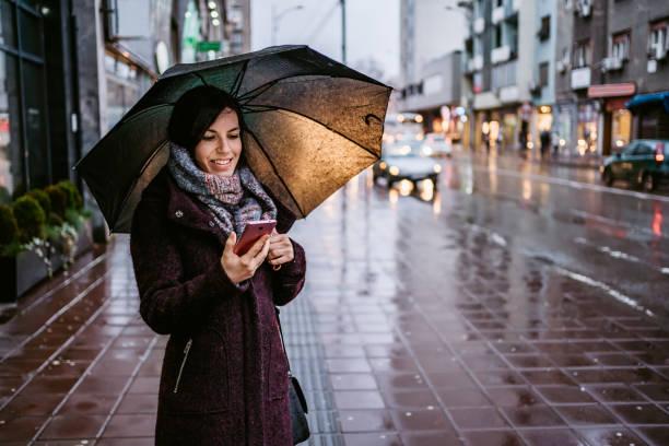 Woman using smartphone downtown in rain stock photo