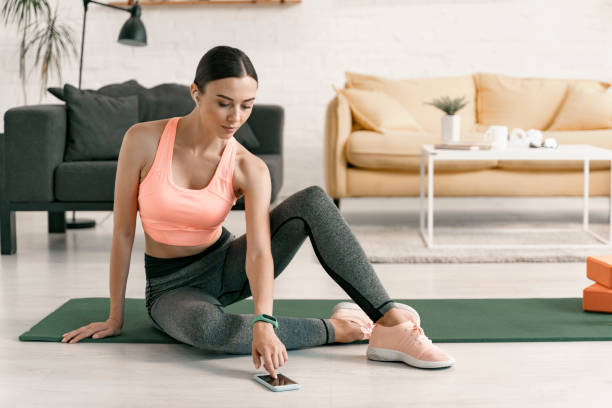 Woman using smartphone during home workout stock photo stock photo