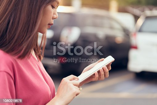 849721378istockphoto Woman using smartphone for the application on car blur background. Concepts for digital technology in everyday Life. 1080019878