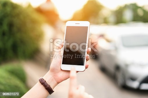 istock Woman using smartphone for the application on car blur background. Concepts for digital technology in everyday Life. 968631070