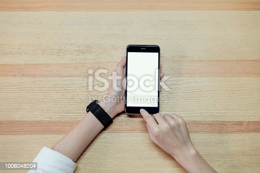 istock Woman using smartphone for the application on table in office. Concepts for digital technology in everyday life. 1006048204