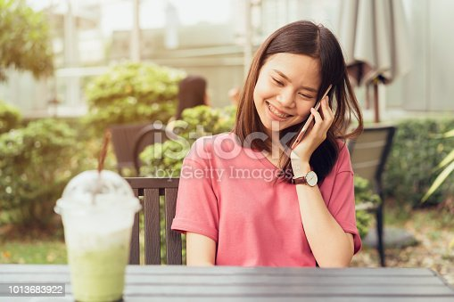 istock Woman using smartphone for the application on table in park cafe. Concepts for digital technology in everyday Life. 1013683922