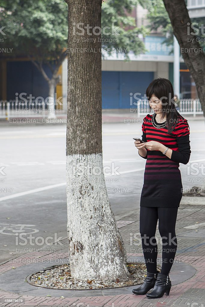 Woman using smartphone in China stock photo