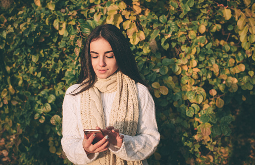 Woman using smartphone in fall. Autumn girl having smart phone conversation in sun flare foliage. Portrait of Caucasian model in forest in fall colors
