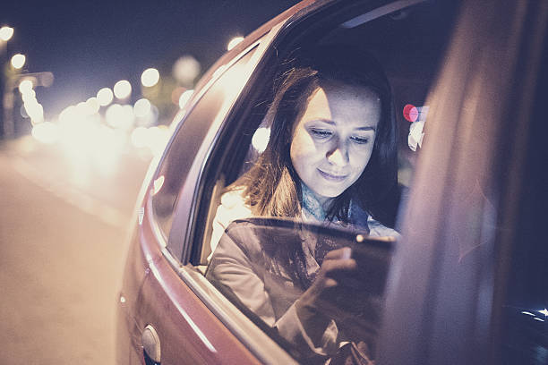 Woman using smartphone in the car stock photo