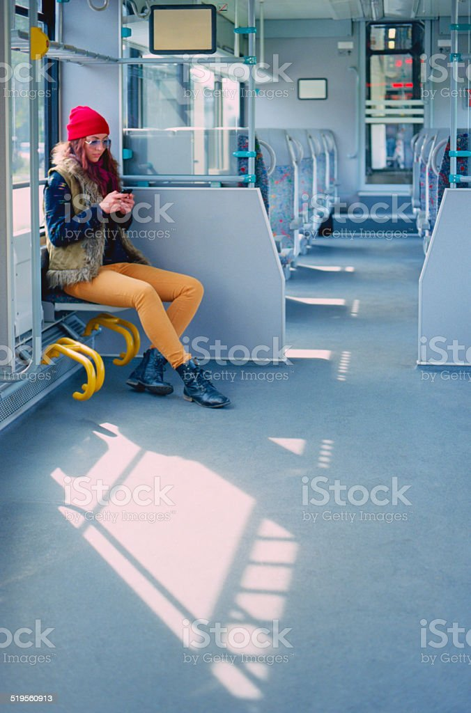 Woman using smartphone in train stock photo
