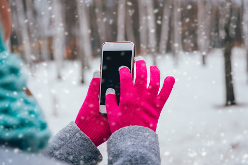 Woman using smartphone in winter with gloves for touch screens. Backgound