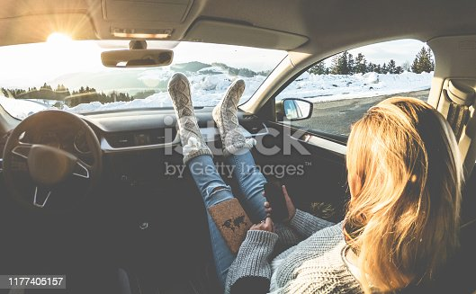 istock Woman using smartphone inside car with feet warm socks on dashboard - Girl relaxing in auto trip reading travel book with snow mountains in background - Traveler concept - Focus on feet 1177405157