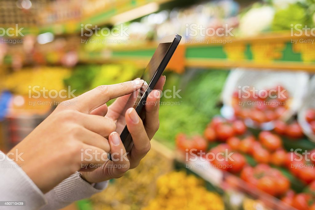 Woman using smartphone near vegetable stand stock photo