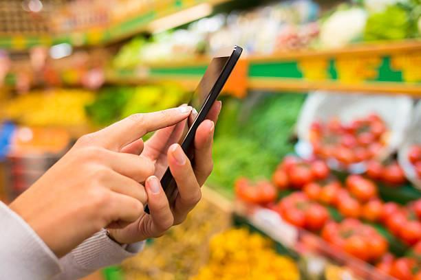 Frau mit smartphone in der Nähe von Gemüse stehen – Foto