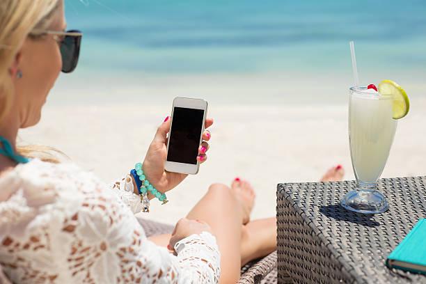 Woman using smartphone on the beach stock photo
