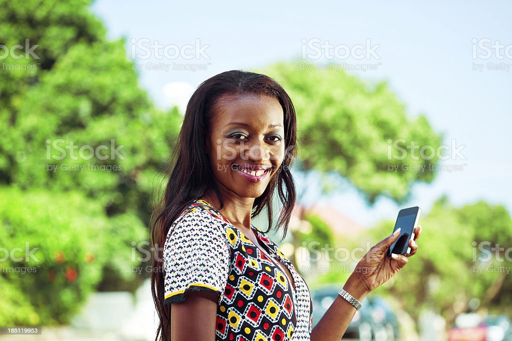 Woman using smartphone Beautiful african woman using smartphone, smiling at the camera. Adult Stock Photo