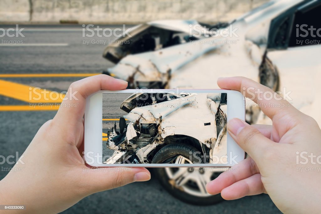 woman using smartphone take photo of car crash accident on the road stock photo