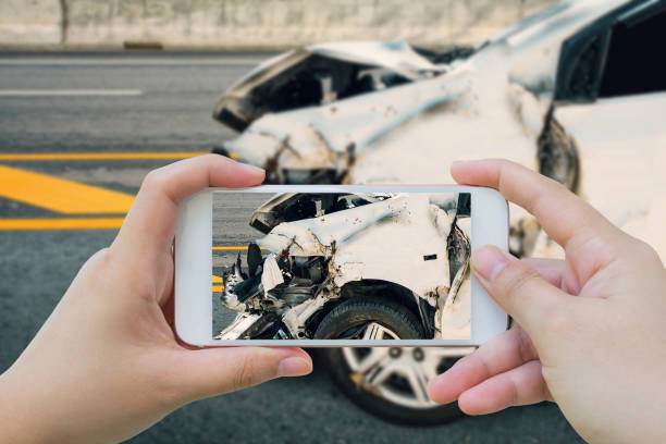 woman using smartphone take photo of car crash accident on the road - car accident stock photos and pictures