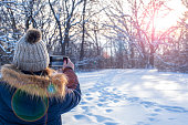 woman taking smartphone photo of sunset over winter landscape