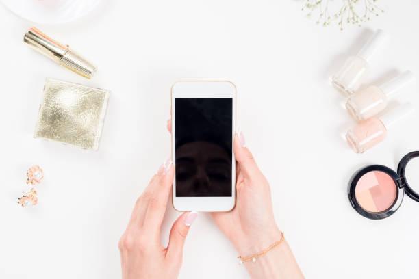 여자 화장품 화이트에 위의 빈 화면으로 스마트폰을 사용 하 여 - 매니큐어 화장품 뉴스 사진 이미지
