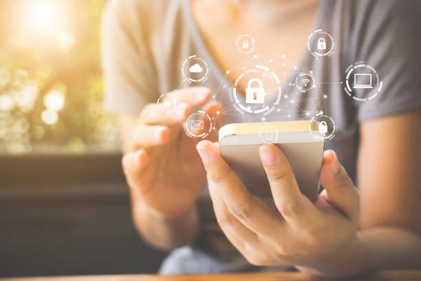 donna che utilizza lo smartphone con icona grafica rete di sicurezza informatica di dispositivi connessi e informazioni sui dati personali - protezione foto e immagini stock