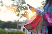 istock Woman using smartphone with shopping bag in hands 665284632