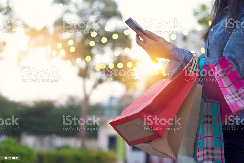 Mujer con smartphone con bolsa en manos - foto de stock