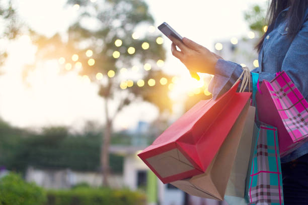 woman using smartphone with shopping bag in hands - shopping stock photos and pictures