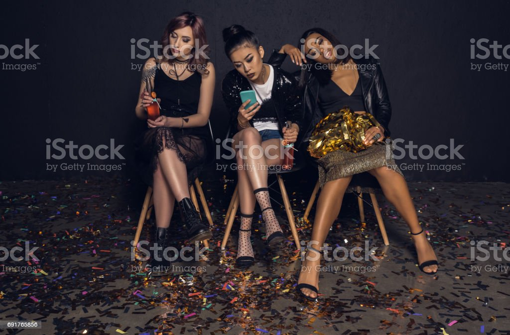 woman using smartphones with bored friends near by at party stock photo