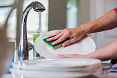 istock Woman using sponge to scrub plate while washing dishes 1068248476
