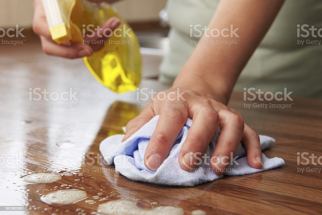 Woman Using Spray Cleaner On Wooden Surface stock photo