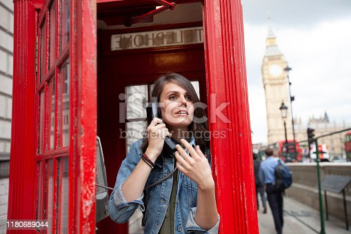 Woman in red outfit using street phone in London.