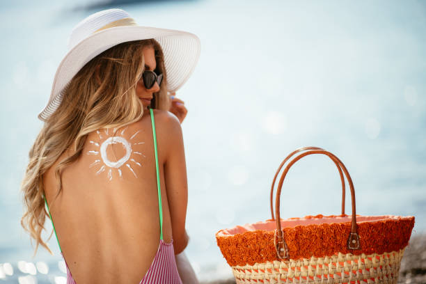 vrouw met behulp van zon crème op het strand - gebruind stockfoto's en -beelden