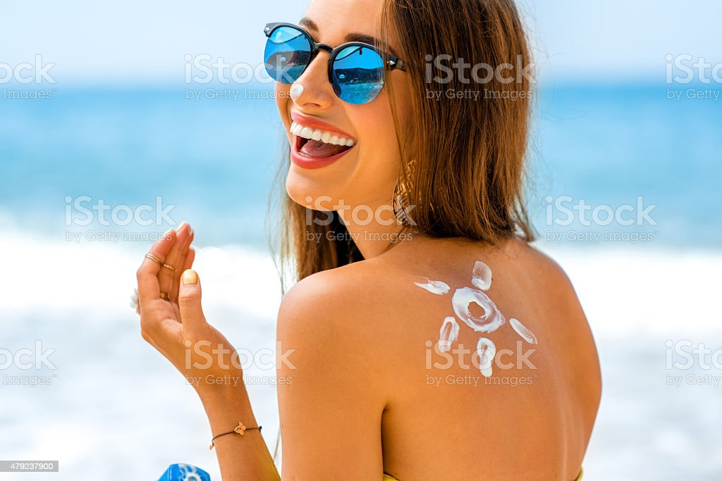 Woman using sun cream on the beach Young woman with sun shape on the shoulder holding sun cream bottle on the beach  2015 Stock Photo