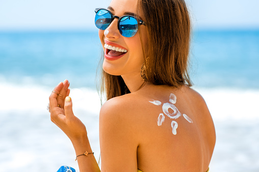 Woman Using Sun Cream On The Beach Stock Photo - Download Image Now