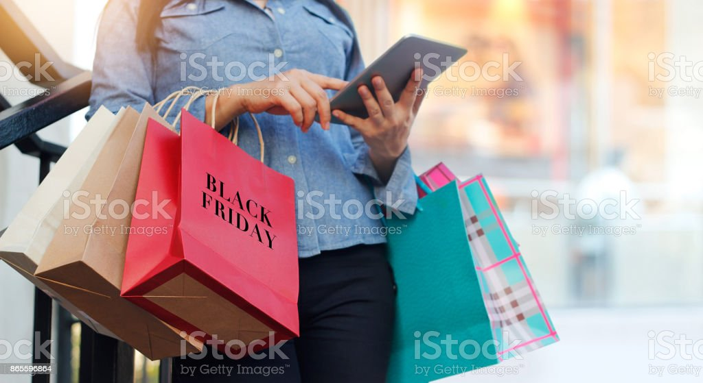 Woman using tablet and holding Black Friday shopping bag while standing on the stairs with the mall background stock photo