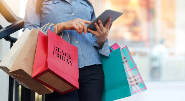 woman using tablet and holding black friday shopping bag while standing on the stairs with the mall background - black friday imagens e fotografias de stock