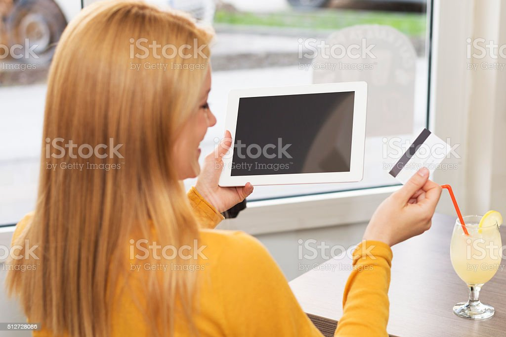 Woman using tablet and holding credit card stock photo