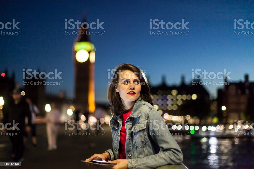 Woman using tablet and walking on bridge stock photo