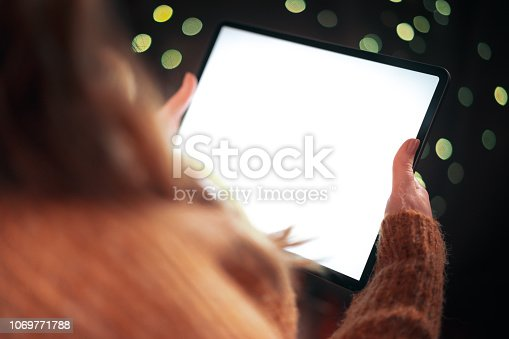 istock Woman using tablet computer at night with dramatic lighting and shallow depth of field 1069771788