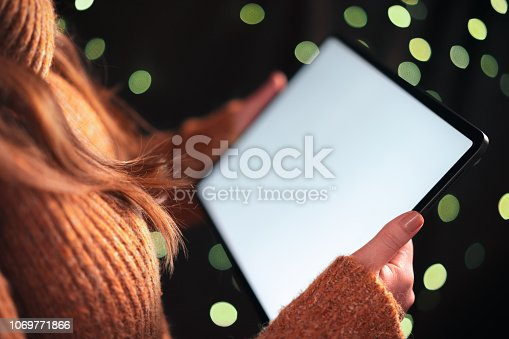 istock Woman using tablet computer at night with dramatic lighting and shallow depth of field 1069771866