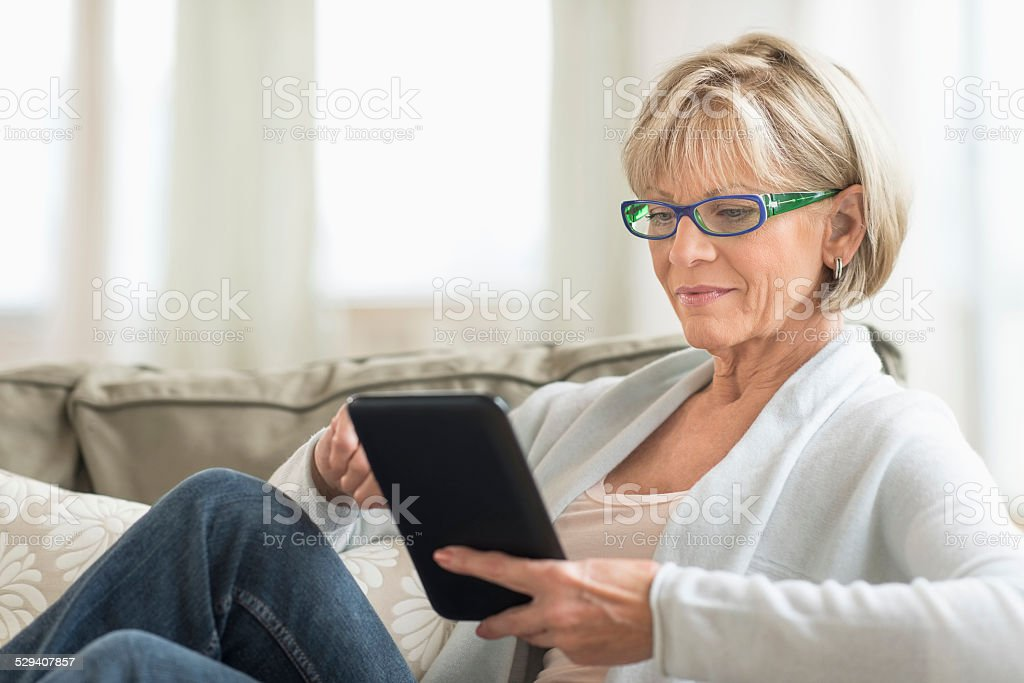 Woman Using Tablet Computer On Sofa stock photo