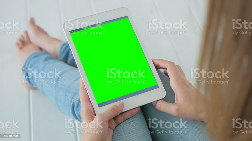 Woman using tablet computer with green screen stock photo