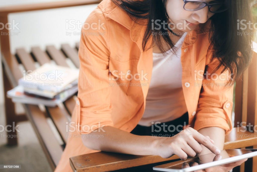 Woman using tablet for working and learning online.