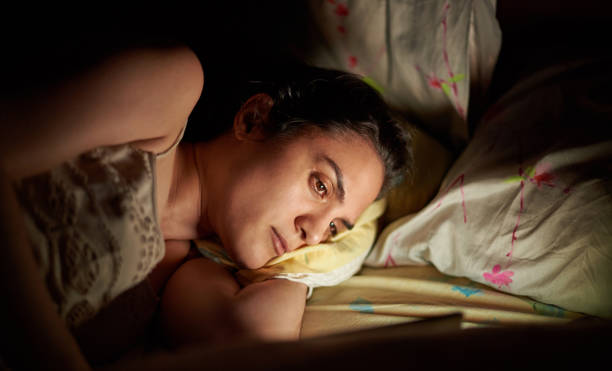 Woman using tablet in bed stock photo