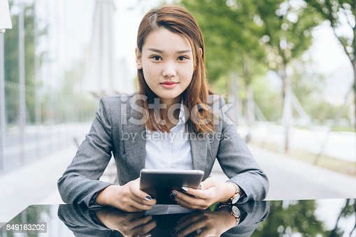 istock woman using tablet PC while sitting at sidewalk cafe 849163202
