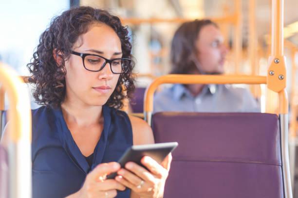 frau mit tablet fahren öffentliche verkehrsmittel - bahn bus stock-fotos und bilder