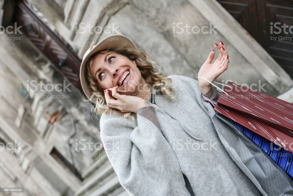 Woman using technology. Young woman comes back from shopping and talking on the phone. stock photo