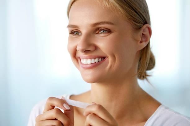 vrouw met behulp van tanden whitening strip voor mooie witte glimlach - tanden bleken stockfoto's en -beelden
