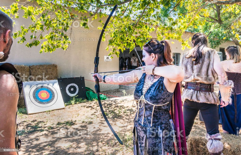 Woman trying out the bow and arrow at the Vikings fair. Various...