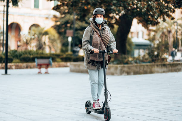 Woman using the scooter during the lockdown stock photo